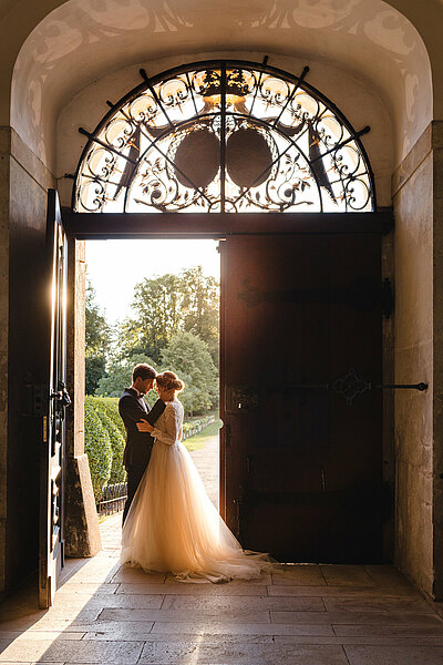 Bridal couple standing at the gate of the castle