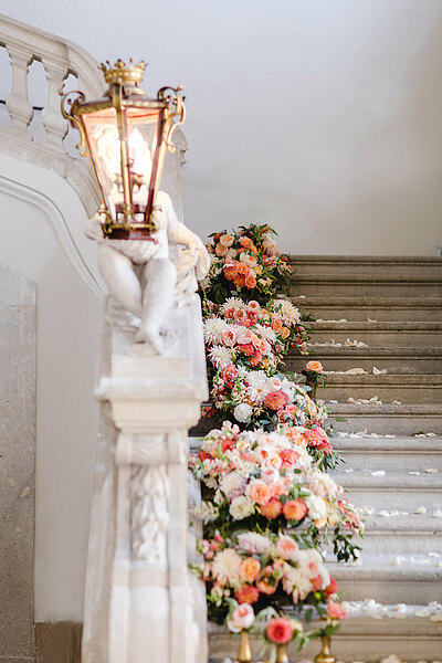 White staircase with lanterns and flowers