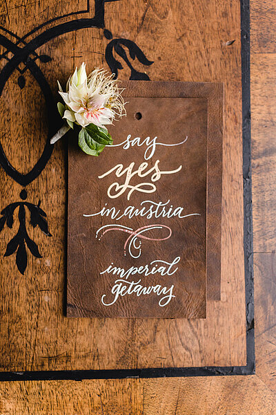 Wedding stationary with flower sitting on a wooden table
