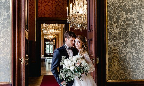 Bridal couple with flowers inside the baroque rooms of Castle Eckartsau